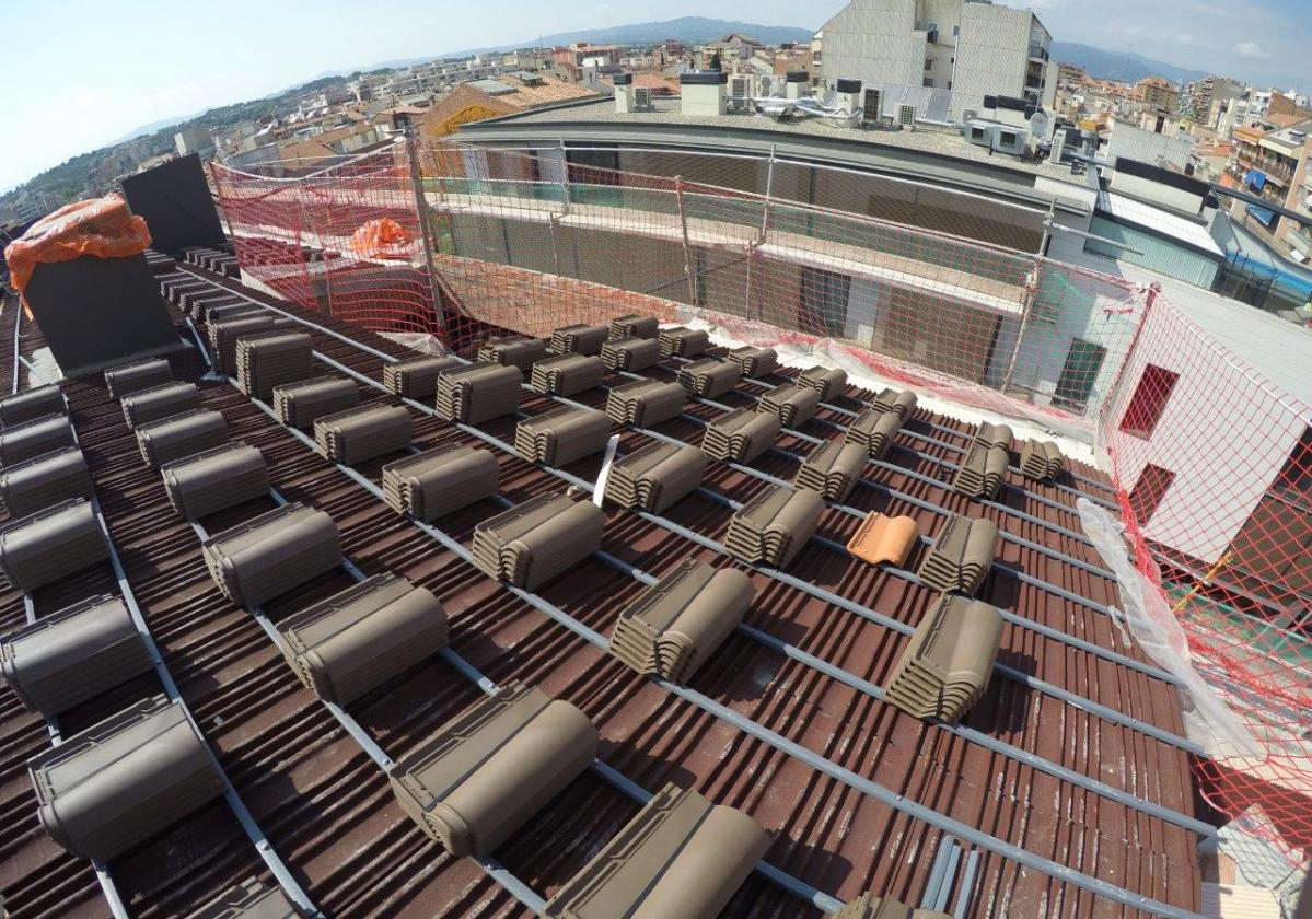 Obra nueva tejado teja mixta en edificio de viviendas con placa asfáltica Onduline Bajo Teja DRS BT150
